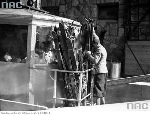 Pasażerowie w wagoniku kolejki linowej. Transport nart w platformie przymocowanej na zewnątrz wagonika, 1 marca 1936 r. / Fot. NAC.gov.pl