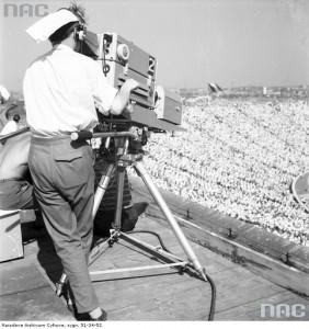 Operator kamery filmuje z korony Stadionu X-lecia pokazy grup regionalnych. Widoczne zapełnione trybuny, 1 sierpnia 1955 r. / Fot. NAC.gov.pl