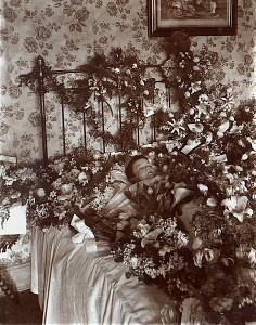 Pośmiertne zdjęcie dziecka otoczonego kwiatami