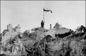 Polska flaga powiewająca na gruzach klasztoru Monte Cassino
