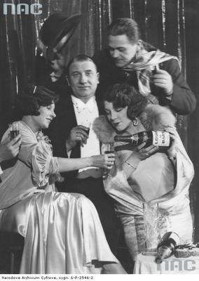 Grupa uczestników balu sylwestrowego 1930/1931. Widoczni aktorzy: Zula Pogorzelska (pierwsza z lewej), Janina Sokołowska i Władysław Walter (drugi z lewej) oraz Eugeniusz Bodo/ fot. nac.gov.pl sygn. 1-P-2546-2