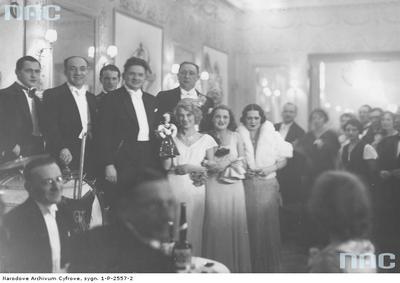 """Grupa uczestników balu sylwestrowego 1932/1933 w kabarecie literackim """"Femina"""" w Warszawie . Widoczni m.in.: pani Irena Horecka (pierwsza z prawej w białej sukni), pani Barbara Gilewska (druga z prawej w białej sukni), pan Ludwik Lawiński (stoi piąty z lewej), Stefan Laskowski (stoi czwarty lewej) oraz dyrektor orkiestry Alfred Melodyst (stoi drugi z lewej)/ fot. nac.gov.pl sygn. 1-P-2557-2"""