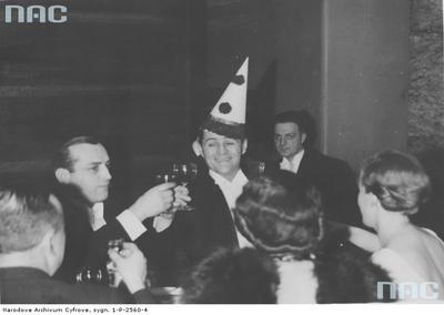Bal sylwestrowy 1935/1936 w lokalu Adria w Warszawie. Na zdjęciu widać  aktorów: Adolfa Dymszę (w czapce) i Tadeusza Olszę (z lewej) podczas wznoszenia noworocznego toastu/ fot. nac.gov.pl sygn. 1-P-2560-4