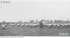 Pokaz grupowy ćwiczeń gimnastycznych przez członków Towarzystwa, na boisku