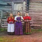 Młode chłopskie dziewczęta w drewnianym domu, we wsi pod Kiriłłowem w obwodzie wołogodzkim. Kobiety częstują gościa jagodami przed wejściem do izby, fot. Siergiej Prokudin-Gorski, 1909 r.