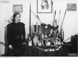 Kurkowska-Spychajowa prezentuje zdobyte trofea. Fotografia wykonana w jej mieszkaniu (listopad 1934 r.). Źródło: NAC, Ilustrowany Kurier Codzienny, sygn. 1-S-1308.